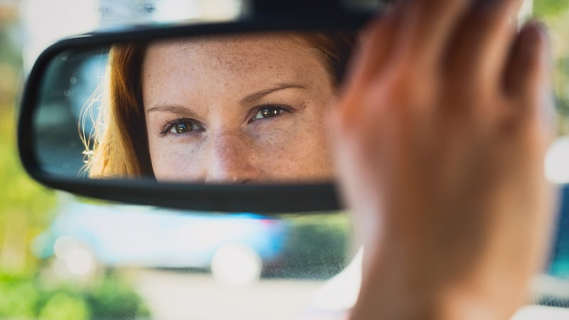 Woman checking behind her in car's rear view mirror.