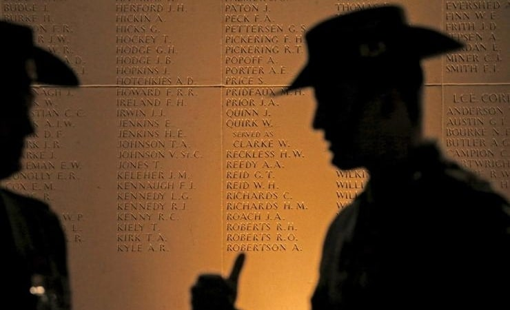 Australian soldiers silhouetted against memorial.