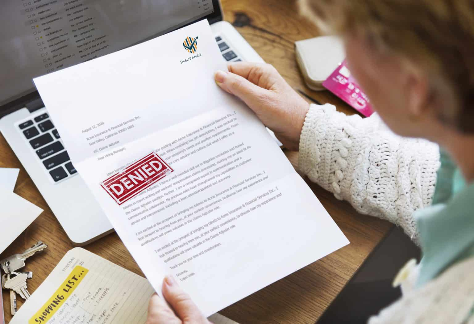 woman opening letter from insurance company saying claim has been denied