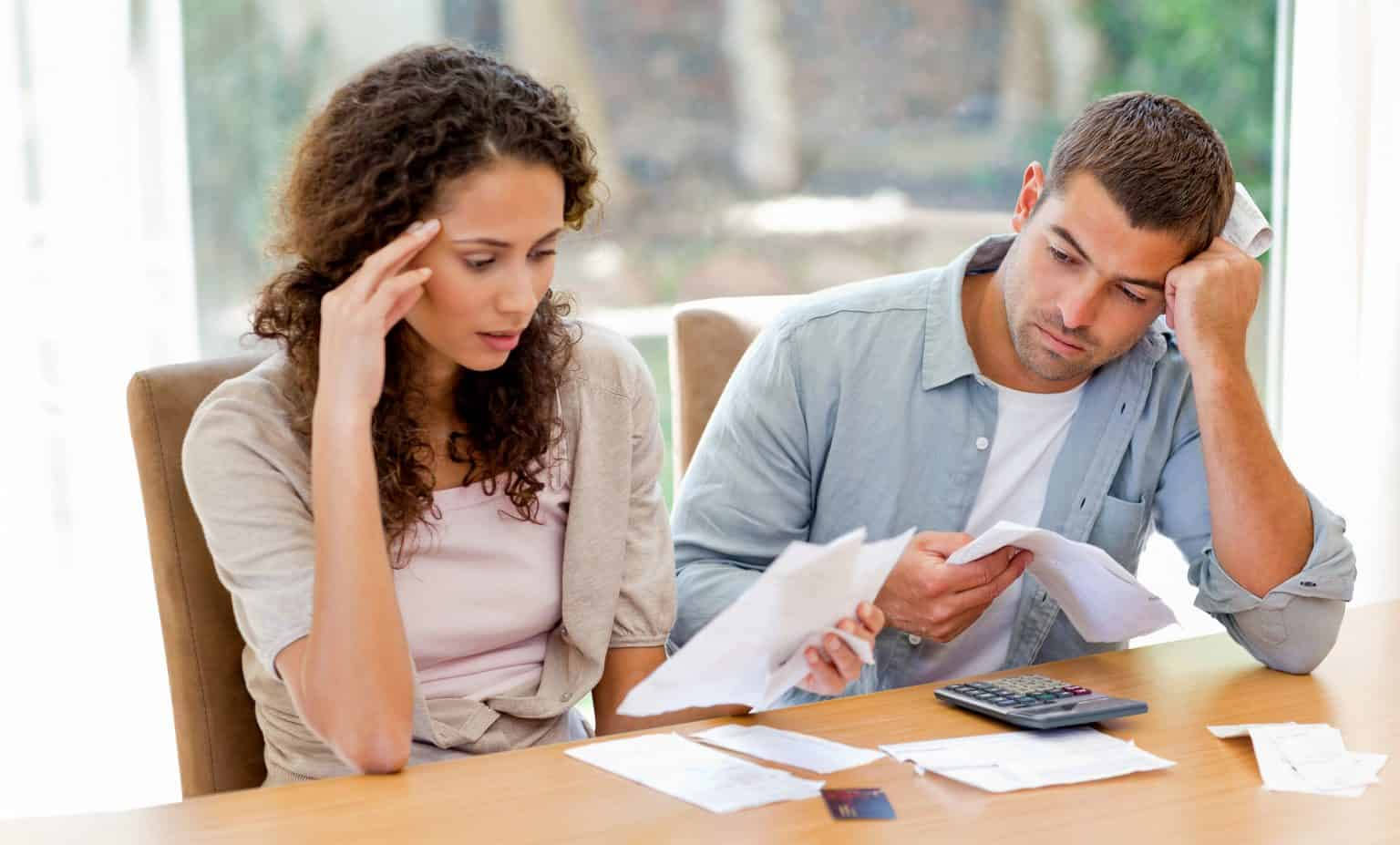 couple unhappy looking at bank documents