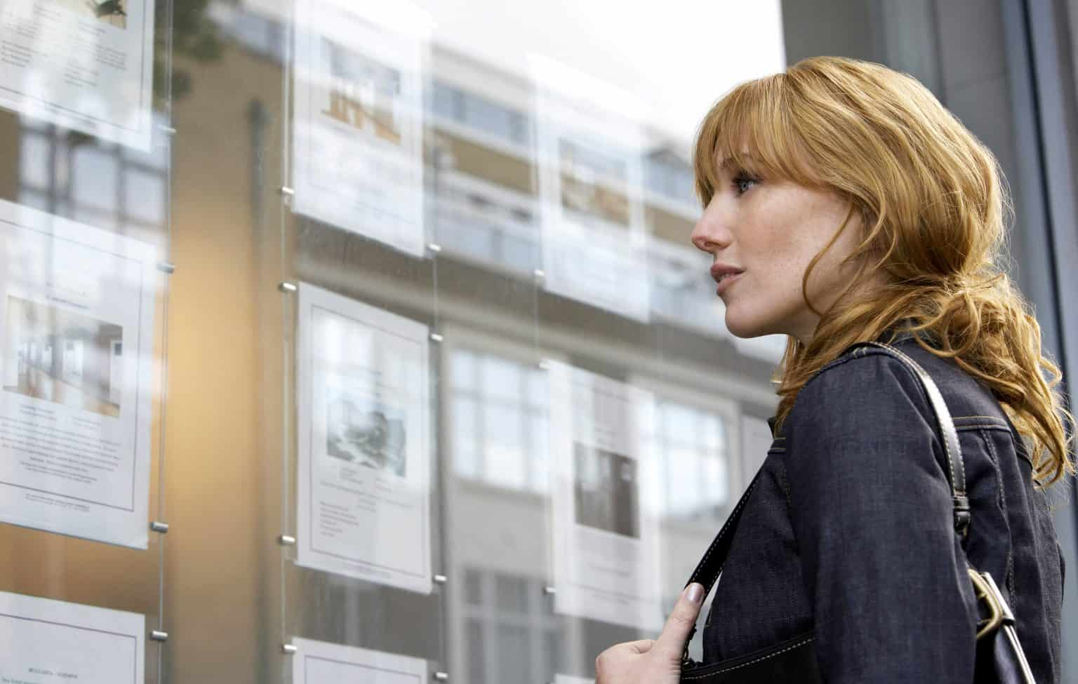 woman looking at real estate window trying to find a rental property